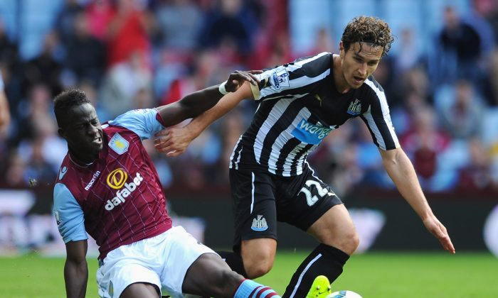 Daryl Janmaat of Newcastle United is tackled by Aly Cissokho of Aston Villa during the Barclays Premier League match between Aston Villa and Newcastle United at Villa Park on August 23, 2014 in Birmingham, England. (Photo by Chris Brunskill/Getty Images)