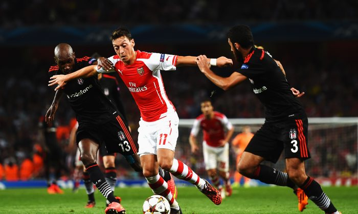 Mesut Oezil (C) of Arsenal holds off the challenge of Atiba Hutchinson (L) of Besiktas and Ismail Koybasl (R) of Besiktas during the UEFA Champions League Qualifier 2nd leg match between Arsenal and Besiktas at the Emirates Stadium on August 27, 2014 in London, United Kingdom. (Photo by Shaun Botterill/Getty Images)