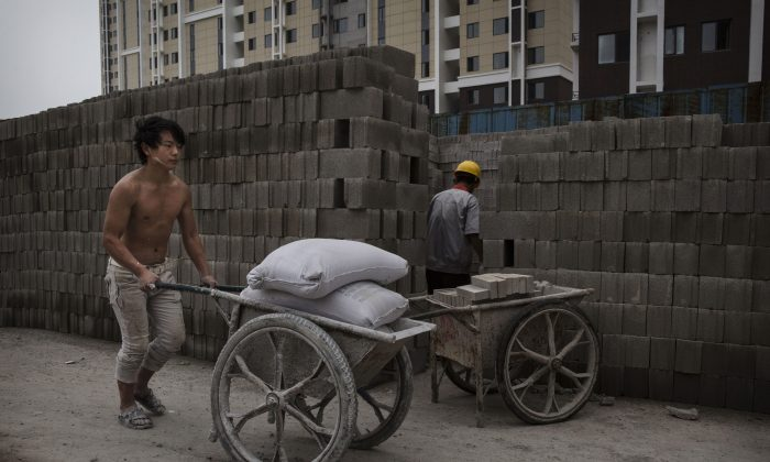 A Chinese construction worker pushes a load of concrete mix at the building site of a new apartment complex on Aug. 29, 2014 in Beijing, China. The deflating of the housing bubble is contributor to a decline in China's economic performance. (Kevin Frayer/Getty Images)