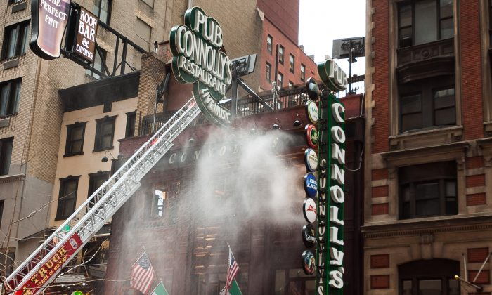 A fast spreading two-alarm fire broke out and destroyed a popular family owned and operated Irish pub, Connolly's Pub and Restaurant, on West 45th Street, Manhattan, Aug. 30, 2014. (Petr Svab/Epoch Times)