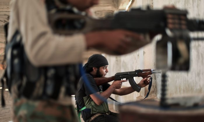Rebel fighters from the Islamic Front, Syria's largest rebel coalition, hold a position on July 13, 2014, during clashes with militants of the Islamic State (IS). (Ahmed Deeb/Getty Images)