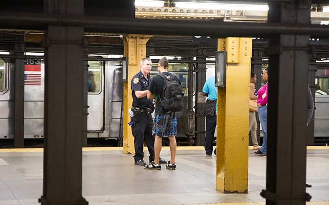 A young man is stopped by a New York police officer at the 34th Penn station subway station in Manhattan on Aug. 7, 2012. Recently, the chief medical examiner's office ruled a homicide in the case of a man who caused a disturbance while high on PCP and died after police restrained him and transported him to a hospital. (Benjamin Chasteen/The Epoch Times)