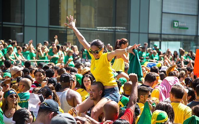 People dressed in Brazil's colors cheer as José Daniel Camillo takes the stage at the 30th anniversary of Brazilian Day New York celebration on Aug. 31, 2014. (Benjamin Chasteen/Epoch Times)