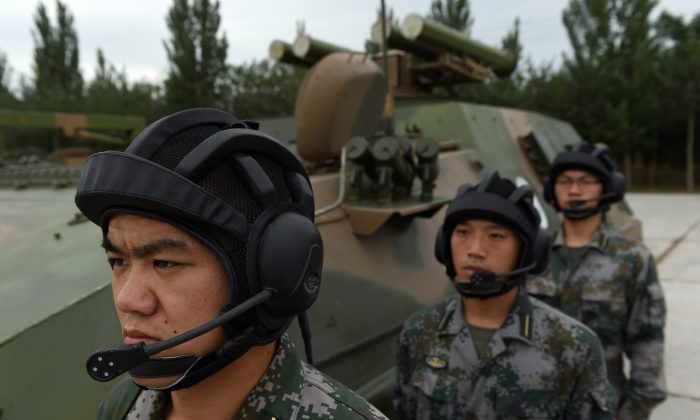 Chinese People's Liberation Army cadets wait beside a T-89 Anti-tank Missile Launcher at the PLA's Armoured Forces Engineering Academy in Beijing on July 22. Xi Jinping, head of the Chiense Communist Party, is calling for a new focus on information warfare. (GREG BAKER/AFP/Getty Images)