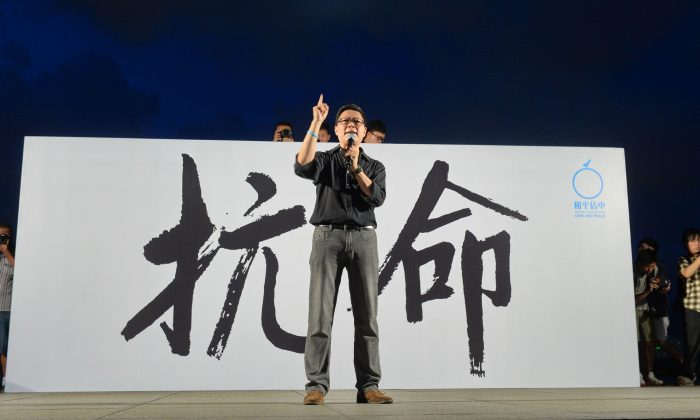 Chan Kin-man, a founder of the Occupy Central movement, speaks at a rally in Tamar Park, Hong Kong, on Aug. 31. Thousands gathered in protest of a recent decision by Beijing to continue restricting democracy in the city-state. (Sung Cheung-lung/Epoch Times)