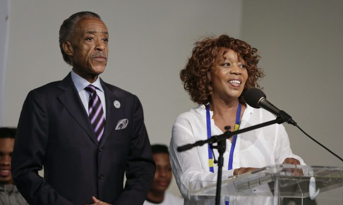 Actress Alfre Woodard, right, speaks as the Rev. Al Sharpton looks on during a rally, Saturday, Aug. 2, 2014, in New York. The rally was held to address the medical examiner's report that came Friday saying Eric Garner's death was caused by a chokehold, a banned police maneuver.  (AP Photo/Julie Jacobson)