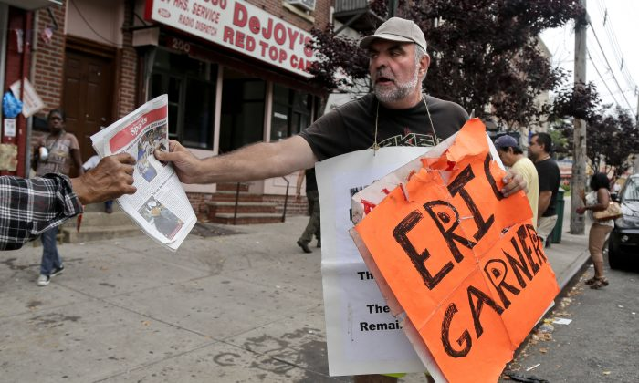 Doug Phaneuf hands a newspaper to a pedestrian while offering information to passers-by about a rally for Eric Garner, Friday, Aug. 1, 2014, in the Staten Island borough of New York. Garner died after he was put in a chokehold while being arrested last month for selling untaxed loose cigarettes. On Friday, the medical examiner ruled Garner's death to be a homicide caused by a police chokehold. (AP Photo/Julie Jacobson)
