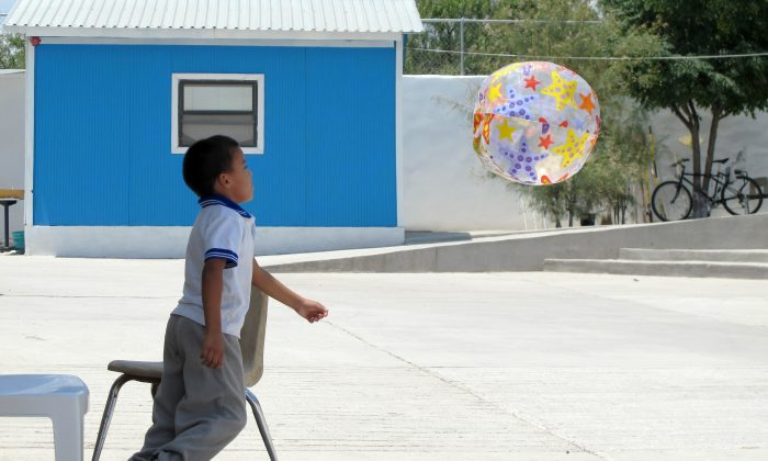 Antony Alvarez, 6, of Honduras plays at the Senda de Vida migrant shelter in Reynosa, Mexico, on Aug. 4, 2014. Alvarez, along with his mother and grandmother, hope to join the thousands of families who have crossed the Rio Grande into the United States. (AP Photo/Christopher Sherman)