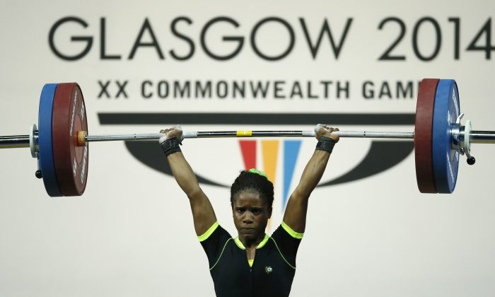This is a Friday, July, 25, 2014 file photo of Chika Amalaha of Nigeria, as she makes good lift during the  women's 53 kg weightlifting competition at the Commonwealth Games Glasgow 2014, in Glasgow, Scotland. The Commonwealth Games Federation says a 16-year-old Nigerian weightlifter has been stripped of her gold medal after a positive doping test it was reported on Friday, Aug. 1, 2014. Amalaha tested positive for diuretics and masking agents after winning the 53-kilogram (117-pound) division last Friday, becoming the youngest ever female to win a weightlifting title at a Commonwealth Games. (AP Photo/Alastair Grant, File)