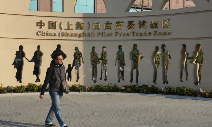 A visitor walks past a design promoting the recently opened Shanghai Pilot Free-Trade Zone on Nov. 28, 2013. Chinese authorities said they will allow foreign-owned hospitals to operate in seven cities and provinces. (Peter Parks/AFP/Getty Images)