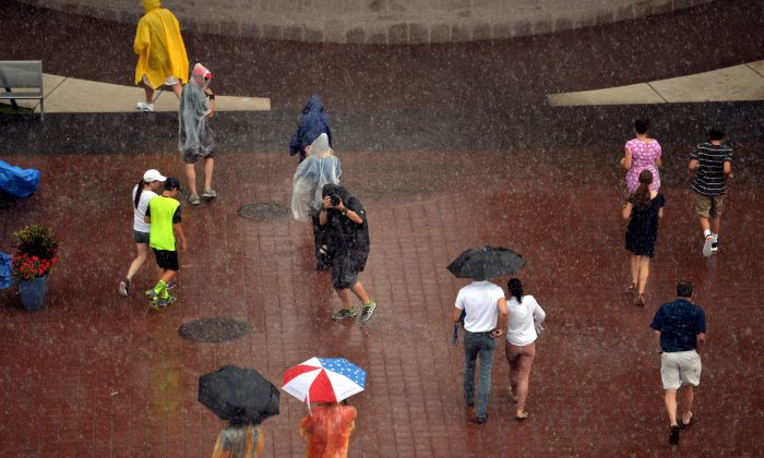 People walk to the exits after rain caused a suspension of play during the 2014 U.S. Open tennis at the USTA Billie Jean King National Tennis Center in Queens, on Sunday. (STAN HONDA/AFP/Getty Images)