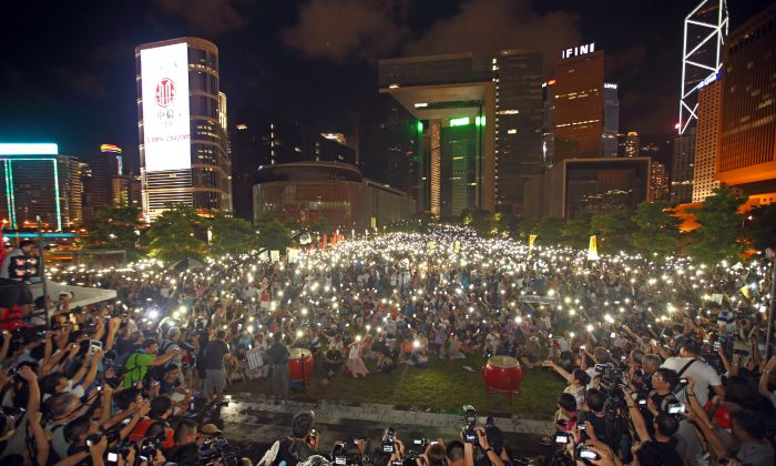 Hong Kong rally on Tamar Park outside the Central Government Offices on Aug 31, 2014, held to protest Beijing's decision to continue to restrict democracy in Hong Kong. Protesters wave lighted mobile phones as candles to show their commitment to civil disobedience. (Poon/Epoch Times)