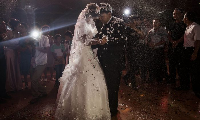A Uyghur couple enjoy their first dance together at their wedding celebration after being married on Aug. 2, 2014, in Kashgar, Xinjiang Uyghur Autonomous Region. A new policy was announced in Xinjiang to give cash and other financial benefits for marriages between the dominant Han Chinese people and minority ethnicities. (Kevin Frayer/Getty Images)
