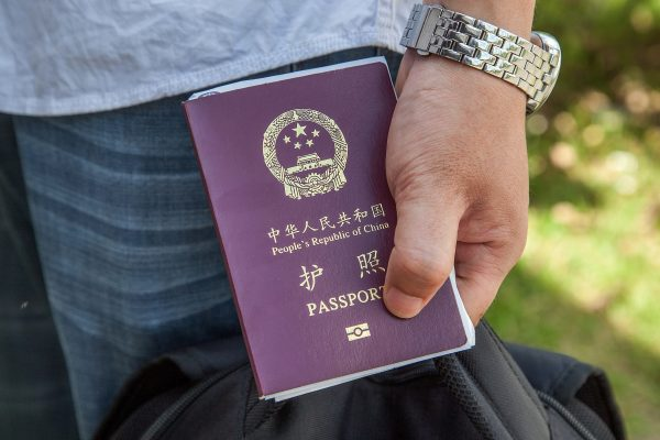 A Chinese national holds a Chinese Passport. Beijing Municipal Organization Department recently launched a new rule that requires officials to hand in their passports, and restricts their traveling abroad with strict approval procedures. (Omar Havana/Getty Images)
