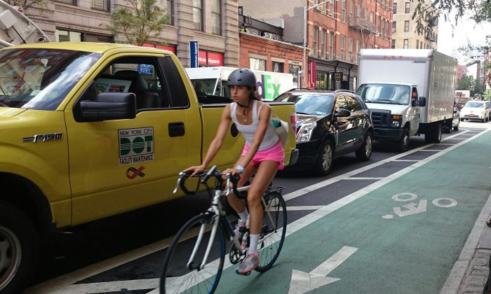 A  cyclist rides on a protected bike lane on Lafayette Street in Soho, Sept. 3. 2014. (Epoch Times)