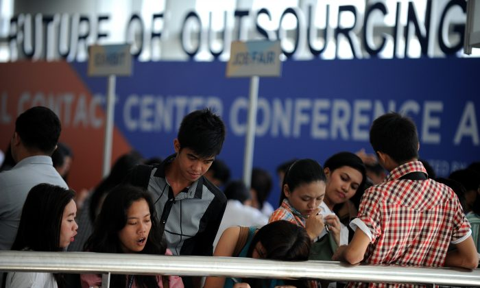 Job seekers fill in their forms at a job fair for call center agents during the International Contact Center Conference and Expo in Manila on Sept. 18, 2012. (Noel Celis/AFP/GettyImages)
