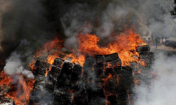 View of forty tons of marijuana seized to alleged drug cartels in a house of the bordering city of Tijuana, Baja California, Mexico being burned by the Mexican Army at their training camp in El Aguaje de La Tuna, Tijuana, Mexico, on May 16, 2014. According to the Interior Ministry, this is the largest seizure of marijuana so far this administration. (Alonso Rochin/AFP/Getty Images)