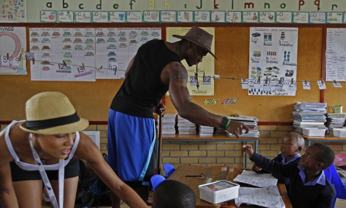 American NFL football star Adrian Peterson, center, from the  Minnesota Vikings, interact with children, as his girl friend, Ashley Brown, left, is seen at the  Mzamomhle Primary School in the township of Philippi situated on the outskirts of  Cape Town, South Africa, Thursday, March 25, 2010. Four American NFL players are on a four day visit to the Western Cape to promote football.  (AP Photo/Schalk van Zuydam)