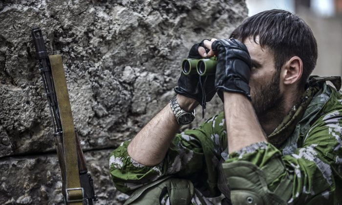 A pro-Russian separatist checks the Ukrainian army position with binoculars at a checkpoint  in the northern outskirts of city of Donetsk, on July 22, 2014. (Bulent Kilic/AFP/Getty Images)