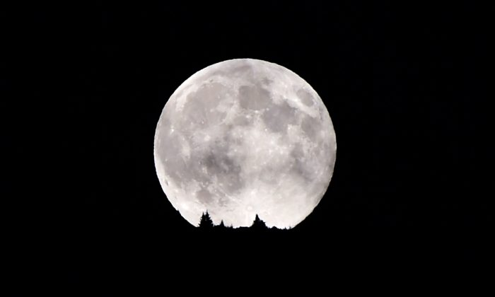 A full moon rises over the Dolomiti mountains in Levico Terme near Trento in north of Italy on August 10, 2014. (AFP/Getty Images)