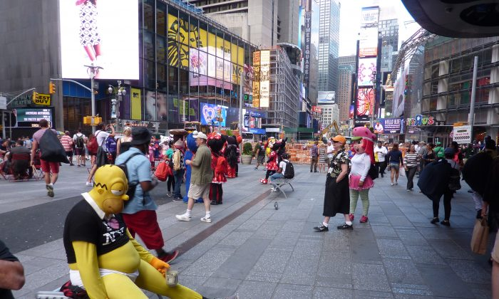A man dressed as Homer Simpson sits with a tip jar in Times Square, on Monday, Sept. 8, 2014. (Shannon Liao/Epoch Times)