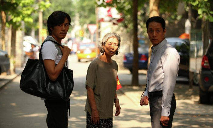 "Deng turns to find the source of her unease as her sons wonder what she is looking for, in a scene from ""Red Amnesia."" (Courtesy of TIFF)"