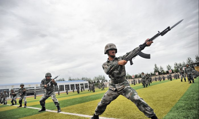 Soldiers perform military exercises in Beijing on July 22, 2014. Massive military exercises extending from July to September may have been directed at keeping a lid on the domestic political situation, argues Chen Pokong. (ChinaFotoPress via Getty Images)