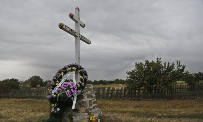 """A commemorative wreath is laid at the foot of a cross, near the wreckage of Malaysia Airlines Flight 17 plane seen outside the village of Hrabove, eastern Ukraine, Tuesday, Sept. 9, 2014. The Dutch team investigating the downing of Malaysia Airlines Flight 17 over Eastern Ukraine says the crash was likely caused by the plane being hit by multiple """"high-energy objects from outside the aircraft."""" The preliminary report published Tuesday by the Dutch Safety Board stopped short of saying the Boeing 777 was shot down by a surface-to-air missile, but its findings appear to point to that conclusion. (AP Photo/Sergei Grits)"""