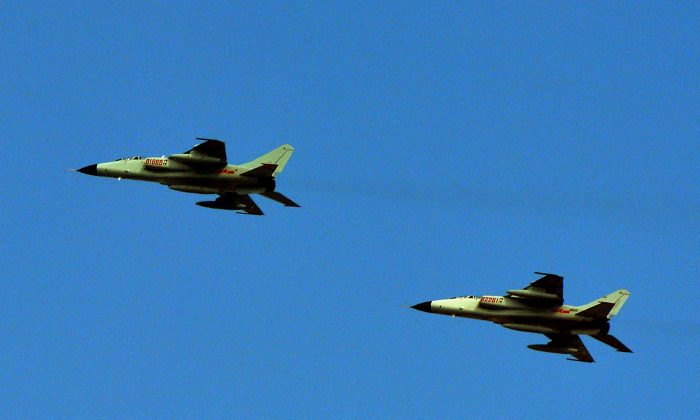 """This photo taken on October 23, 2013 shows Chinese People's Liberation Army (PLA) fighter jets leaving their base in Shanghai. Beijing's behaviour in its row with Tokyo over disputed islands is jeopardising peace, Japan's defence minister said on October 29, days after China warned a reported plan to shoot down its drones would constitute """"an act of war"""".  (Mark Ralston/AFP/Getty Images)"""