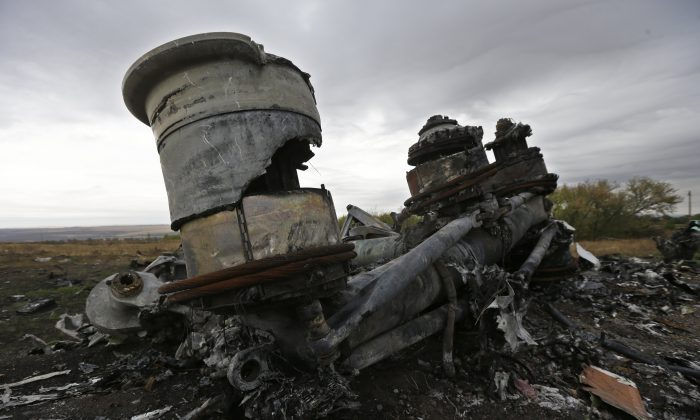 """Pieces of the Malaysia Airlines Flight 17 plane are seen near village of Hrabove, eastern Ukraine, Tuesday, Sept. 9, 2014. The Dutch team investigating the downing of Malaysia Airlines Flight 17 over Eastern Ukraine says the crash was likely caused by the plane being hit by multiple """"high-energy objects from outside the aircraft."""" The preliminary report published Tuesday by the Dutch Safety Board stopped short of saying the Boeing 777 was shot down by a surface-to-air missile, but its findings appear to point to that conclusion. (AP Photo/Sergei Grits)"""
