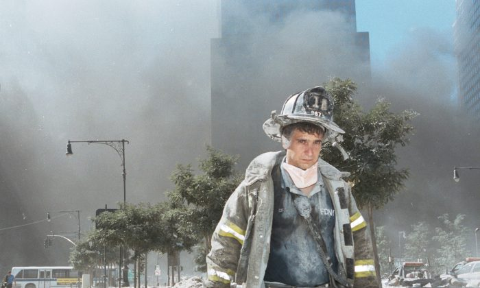 An unidentified New York City firefighter walks away from Ground Zero after the collapse of the Twin Towers in New York on Sept. 11, 2001. (Anthony Correia/Getty Images)