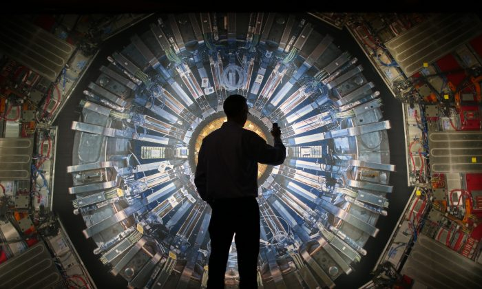 A visitor takes a phone photograph of a large back lit image of the Large Hadron Collider (LHC) at the Science Museum's 'Collider' exhibition in London, England, on Nov. 12, 2013. (Peter Macdiarmid/Getty Images)