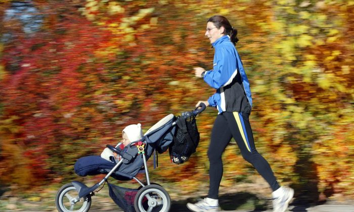A mother jogs in a park while pushing a pram. Women living in areas with lots of green space have better birth outcomes, according to new research. (Jens-Ulrich Koch/AFP/Getty Images)