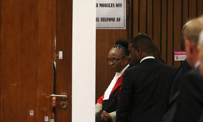 In this Friday, May 9, 2014 file photo Judge Thokozile Masipa, to right of door in red cape, and her advocates examine the bullet-riddled toilet door up close during expert forensics evidence being given at the Oscar Pistorius murder trial in in Pretoria, South Africa. Judge  Masipa is expected to announce her verdict after summing up Thursday and Friday  in Pistorius' murder trail after scrutinizing evidence given by 37 witnesses in a court transcript running to thousands of pages in a drama that has played out over six months.  (AP Photo/Themba Hadebe, Pool, File)