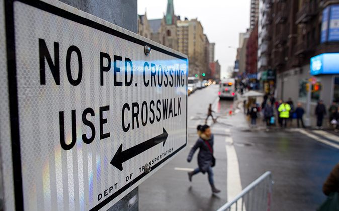 After crossing outside a crosswalk, a pedestrian runs toward a crosswalk at the busy intersection of W. 96th Street and Broadway in the Upper West Side, Jan. 27. (Craig Ruttle/AP)