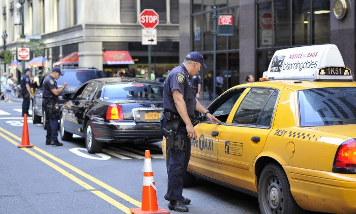 A New York police officer inspects a taxi outside the Grand Central Terminal in New York on Sept. 09, 2011. (Mladen Antonov/AFP/Getty Images)