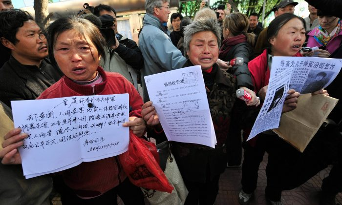 """Chinese petitioners show documents detailing their grievances in Beijing. Recently in Xinjiang Province, a group of local residents broke into a """"black jail"""" to rescue a Chinese petitioner illegally detained by security officials. (Teh Eng Koon/AFP/Getty Images)"""