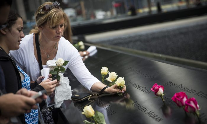 A woman places flowers on the name of a loved one during the memorial observances held at the site of the World Trade Center on September 11, 2014, in New York City. (Andrew Burton/Getty Images)
