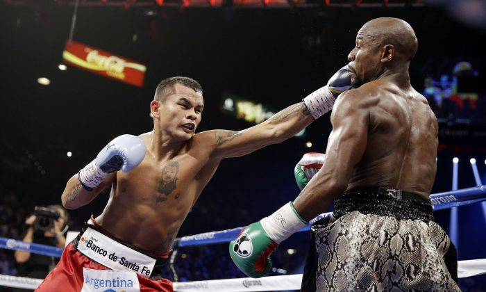 Marcos Maidana punches Floyd Mayweather, right, during their WBA welterweight and WBC super  welterweight title fight, Saturday, Sept. 13, 2014, in Las Vegas. (AP Photo/John Locher)