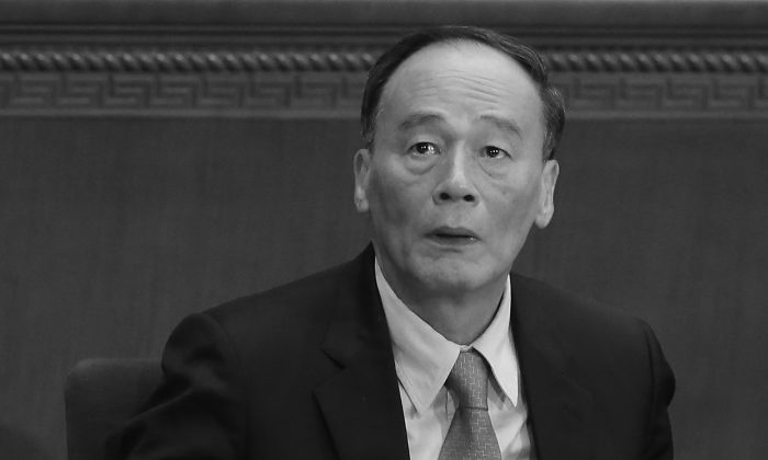 China's Politburo Standing Committee member Wang Qishan attends the opening session of the National People's Congress at the Great Hall of the People in Beijing on March 5, 2014. (Feng Li/Getty Images)