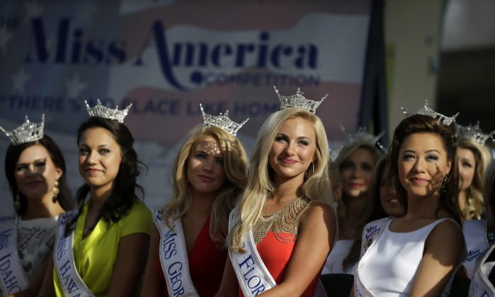 Miss America Pageant contestants, from left, Miss Idaho Sierra Sandison, Miss Hawaii Stephanie Steuri, Miss Georgia Maggie Bridges, Miss Florida Victoria Cowan, and Miss District of Columbia Teresa Davis watch arrival ceremonies Wednesday, Sept. 3, 2014, in Atlantic City, N.J. Miss America contestants from all 50 states, the District of Columbia, Puerto Rico and the U.S. Virgin Islands will appear Wednesday afternoon at the traditional welcoming ceremony across from Boardwalk Hall. (AP Photo/Mel Evans)