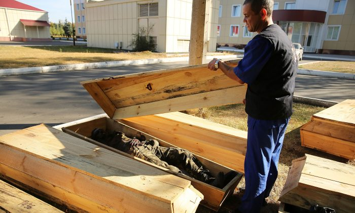 Morgue worker Sergiy Pilipenko inspects the coffins of unclaimed bodies, both civilians and soldiers, outside of the city morgue in Luhansk, Ukraine, on Sept. 14, 2014. Luhansk, a separatist-held city close to the border with Russia, has witnessed some of the heaviest fighting between Russian-backed separatist soldiers and Ukrainian troops. (Spencer Platt/Getty Images)