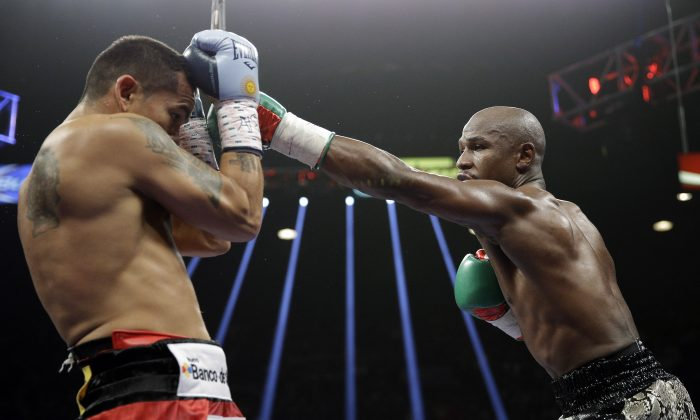 Floyd Mayweather punches Marcos Maidana, left, during their WBA welterweight and WBC super  welterweight title fight, Saturday, Sept. 13, 2014, in Las Vegas. (AP Photo/John Locher)