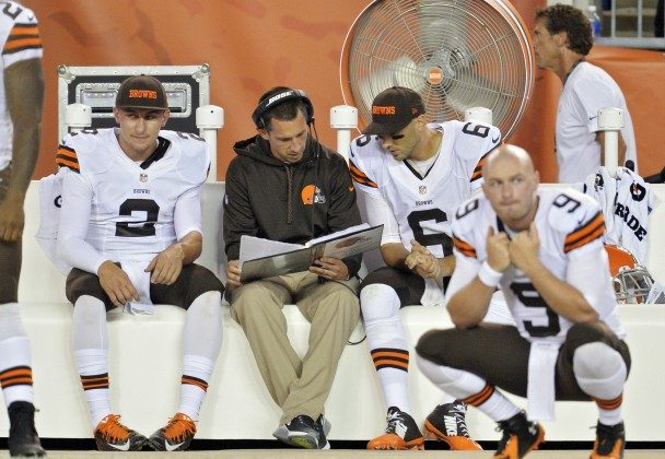 FILE - In this Aug. 23, 2014, file photo, Cleveland Browns quarterbacks Johnny Manziel (2) listens in as offensive coordinator Kyle Shanahan, center, talks with Brian Hoyer (6) on the sidelines in the fourth quarter of a preseason NFL football game against the St. Louis Rams in Cleveland. Manziel doesn't view himself as the Browns' savior, but almost everyone else does. The dynamic rookie quarterback will begin the season as Cleveland's second-string quarterback, but it may not be long before he's moved ahead of Hoyer, who already seems to be looking over his shoulder. (AP Photo/David Richard, File)