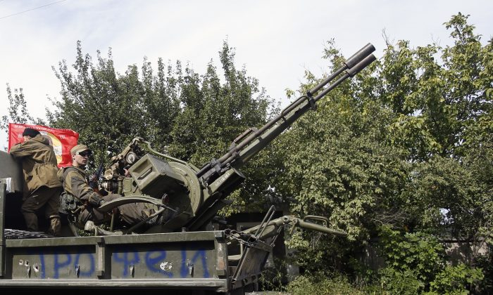 A Pro-Russia rebels truck with an anti-aircraft weapon is driven in a parade in the town of Luhansk, eastern Ukraine, Sunday, Sept. 14, 2014. Some semblance of normality is returning to parts of eastern Ukraine after a cease-fire agreement sealed between Ukrainian government forces and separatist rebels earlier this month, although exchanges of rocket fire remain a constant in some areas. (AP Photo/Darko Vojinovic)