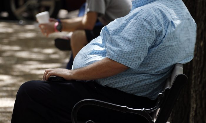 In this Sept. 4, 2014, photo an overweight man rests on a bench in Jackson, Miss. Rising numbers of American adults have the most dangerous kind of obesity, belly fat, despite evidence that overall obesity rates may have plateaued, government data shows. Abdominal obesity affects 54 percent of U.S. adults, versus 46 percent in 1999-2000, and the average waist size crept up an inch, too, according to the most recent statistics. (AP Photo/Rogelio V. Solis)