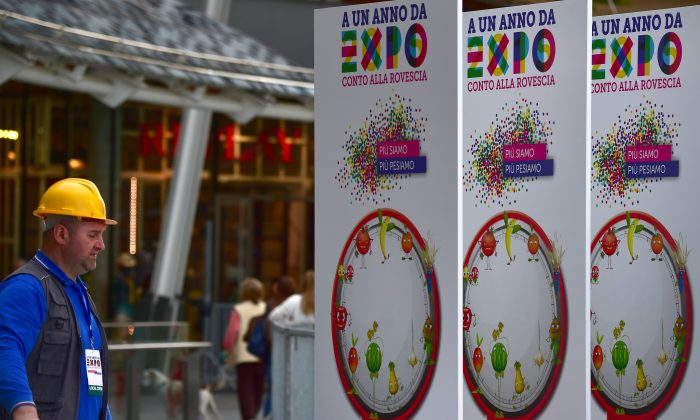 A worker installs signs promoting the 2015 universal exhibition (Expo 2015) on April 29, 2014, in Milan. Expo 2015 is the next scheduled Universal Exposition and will be hosted by the city of Milan, Italy, between May 1st and October 31, 2015. (Giuseppe Cacace/AFP/Getty Images)