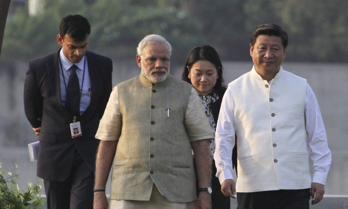 Indian Prime Minister Narendra Modi (2nd-L) and Chinese Communist Party leader Xi Jinping (R) walk on the Sabarmati River front in Ahmadabad, India, on Sept. 17, 2014. Xi is on a three day visit aimed at improving ties and investment with India. (AP Photo/Ajit Solanki)