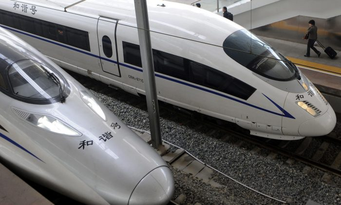 A passenger walks past a high-speed train at a railway station in Nanjing in eastern China. China used controversial industrial policies that are exempt from Canada's new investment deal with China to force foreign firms to share intellectual property and know-how. This helped push China's domestic train industry to become globally competitive. (AP Photo)