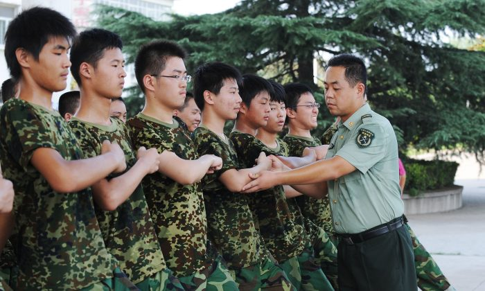 Chinese students practice marching under the supervision of a People's Liberation Army soldier during their one week of first-year high school military service at a military base in Hefei, east China's Anhui province on Aug. 5, 2010. Recent scandals involving the military training of students have provoked public anger at the programs. (STR/AFP/Getty Images)